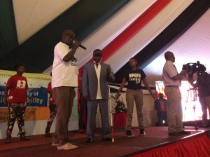 Paul Mugambi 'Mpofu number One' performing with the Chief Guest Hon Kazungu(In blindfold and white cane) at the event