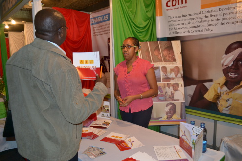 Michelle Petters CBM Emergency Programme Assistant (East Africa) educating a visitor at the CBM stand on who CBM is and its mandate to assist children with disabilities